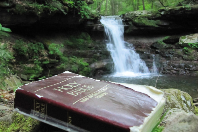 Holy Bible pictured near an outdoor waterfall.